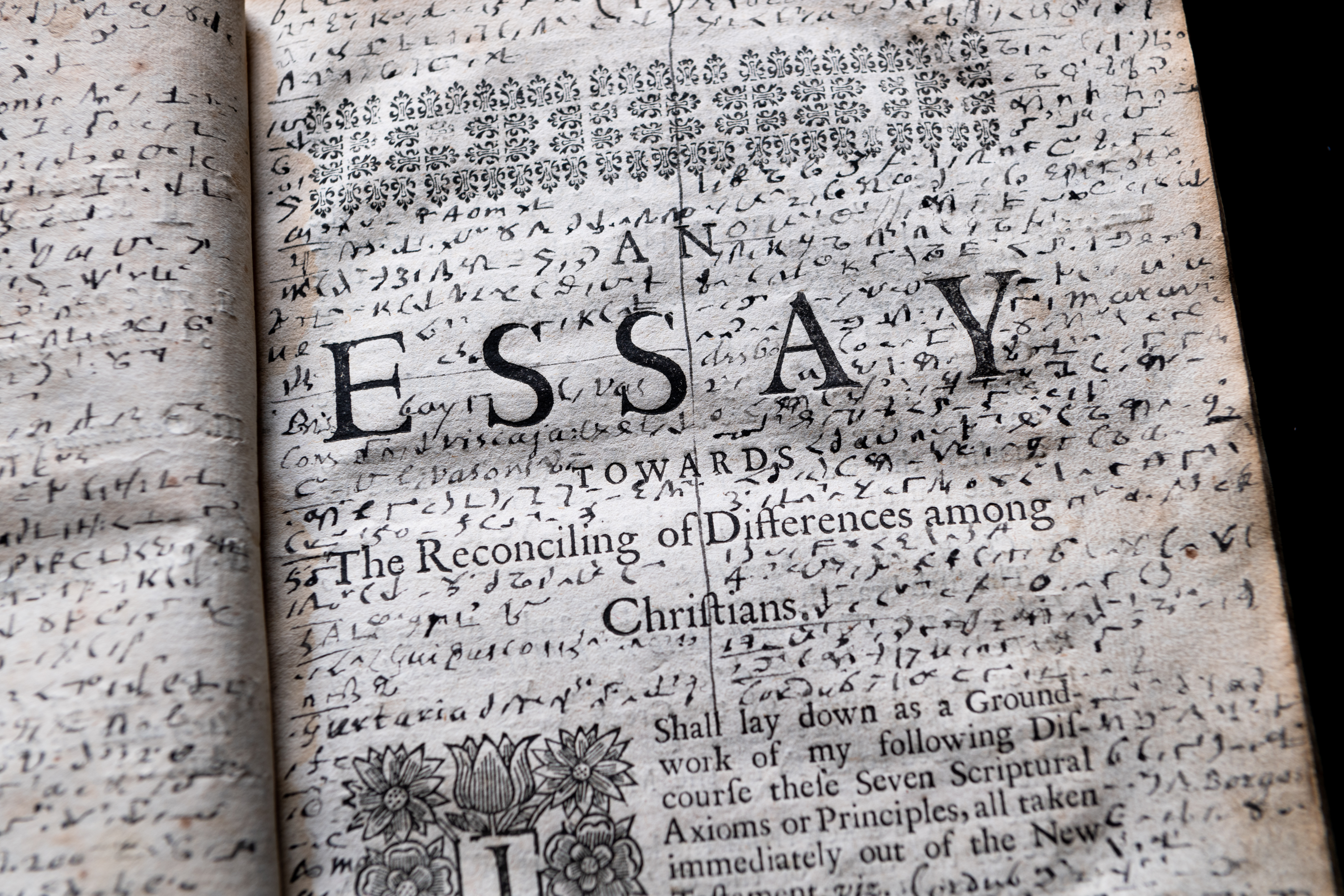 Detail of a printed book shows title page with manuscript notations throughout the blank spaces on the page.