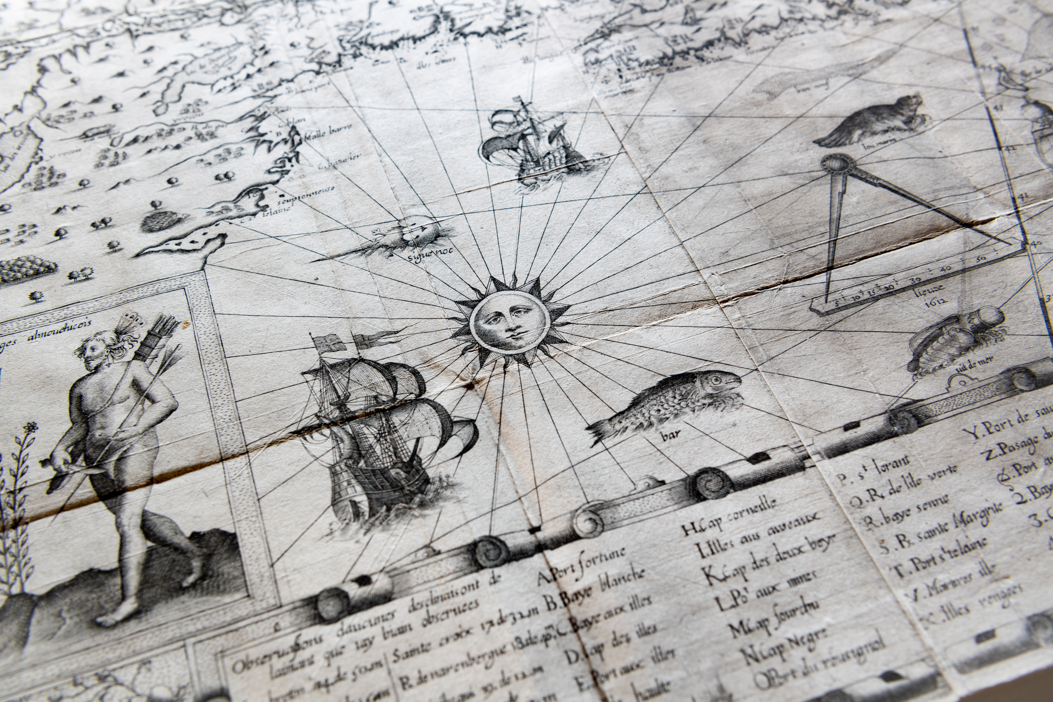 Detail of a printed map shows decorative elements such a sun, a person carrying arrows, ships and fish at sea, a scale, and a key with text in French at the bottom of the map.
