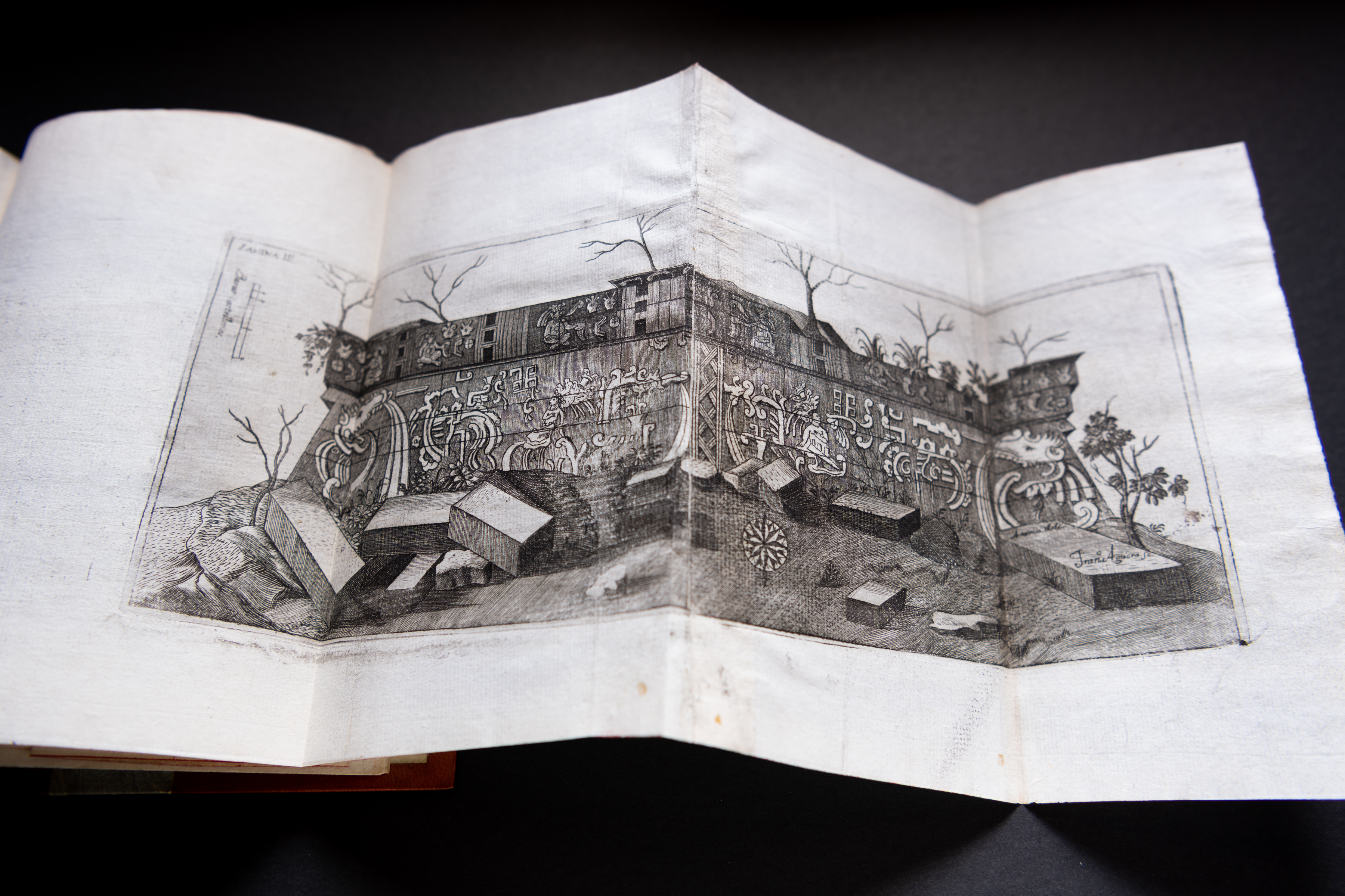 Detail of a printed book shows a fold-out illustration of stones outside of a buildings facade.