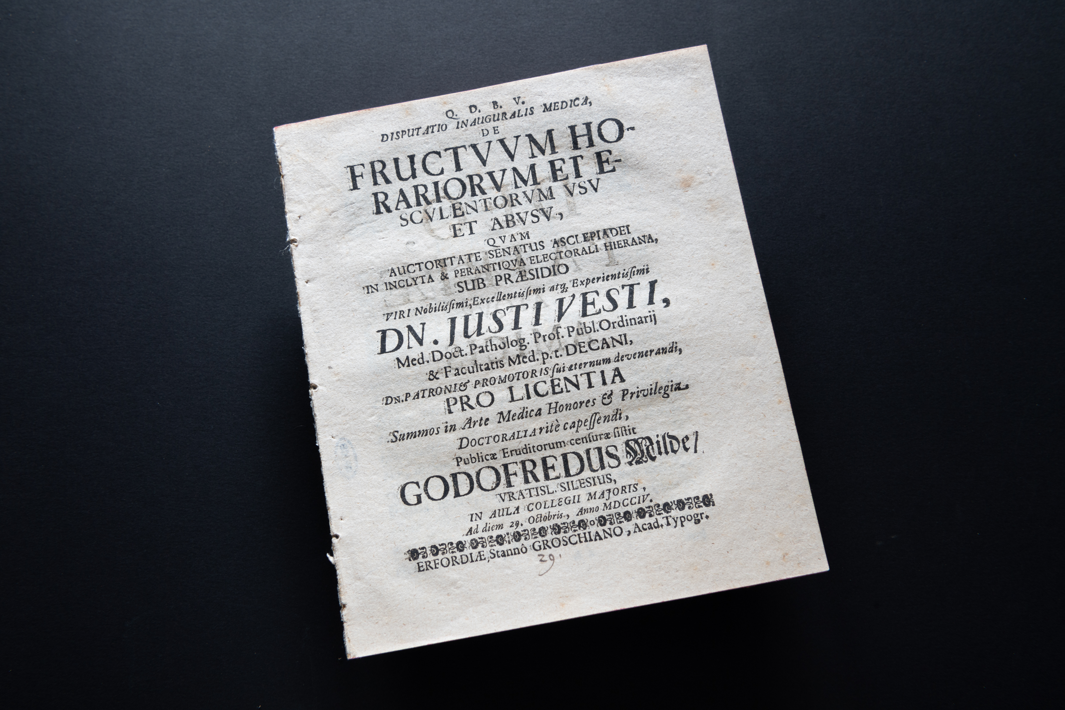 Detail of a printed book shows a title page with text in Latin.