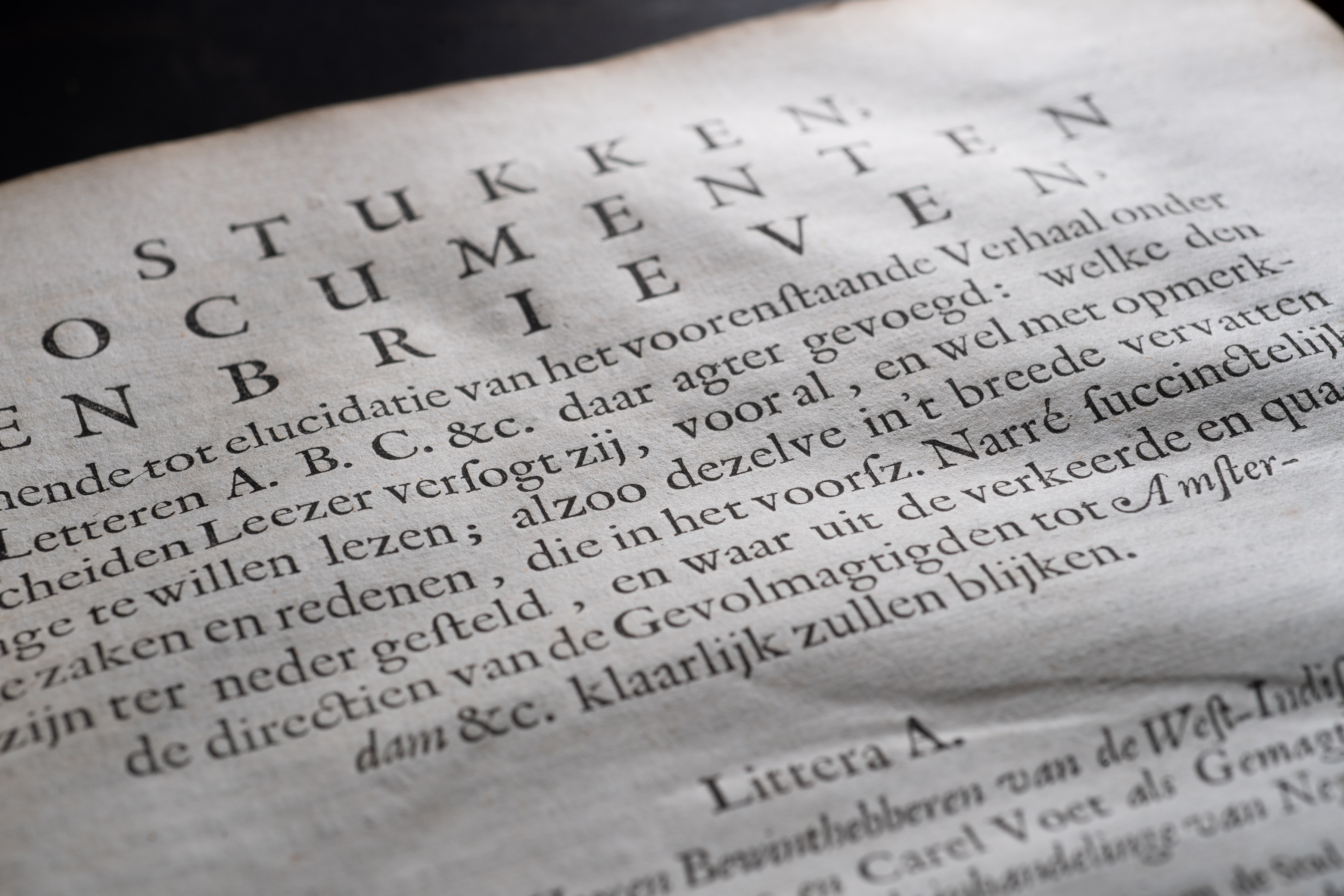Detail of a printed book shows a page with text in Dutch.
