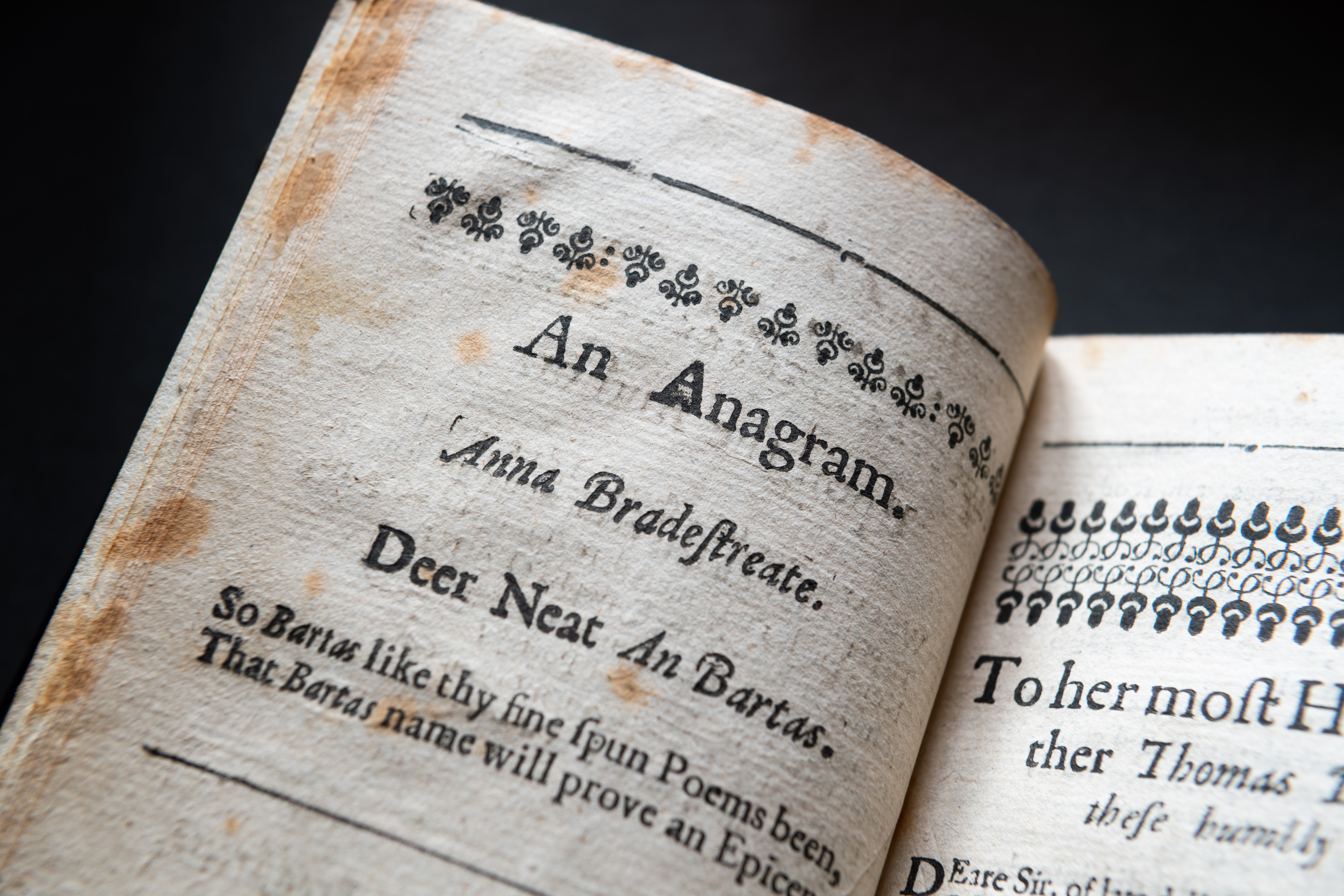 "Detail of a printed book shows worn papers and header text reading ""An Anagram. Anna Bradestreate"" and other text in English."