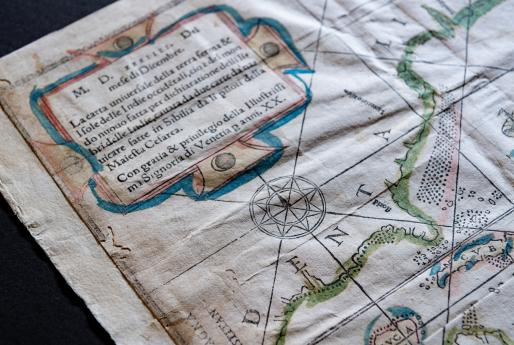 "Detail of a woodcut, hand-colored map depicting North and South America. Visible details include Cuba, written as ""CVBA"", a compass rose, and text in Italian."
