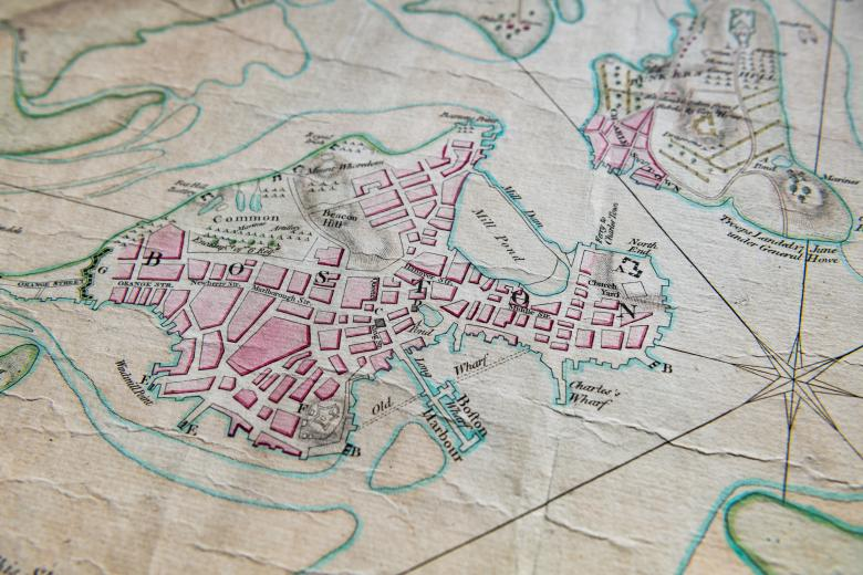 """Detail of a hand colored, engraved map of Boston, Massachusetts shows details such as """"Boston Harbor,"""" """"Mill Pond,"""" and """"Charles's Wharf."""" Pink, green, and blue colors help differentiate geographical features."""