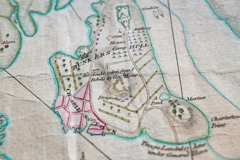 """Detail of a hand colored, engraved map of Boston, Massachusetts shows details such as """"Bunker Hill"""" and """"Charlestown."""" Pink, green, yellow, and blue colors help differentiate geographical features."""