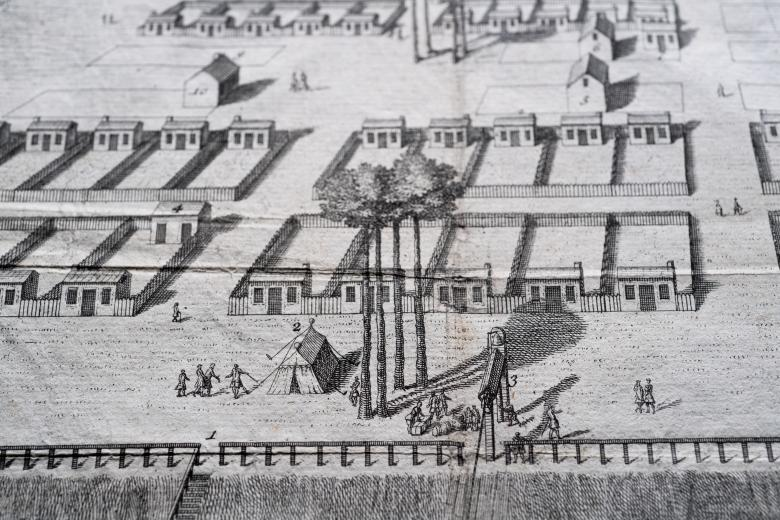 Detail of an engraved map shows people standing around a tent that is surrounded by a grid layout.