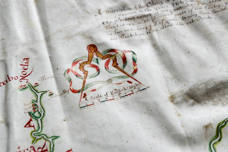 Detail of hand colored, manuscript map shows a scale in red and green ink and out-of-focus text in the top right corner.