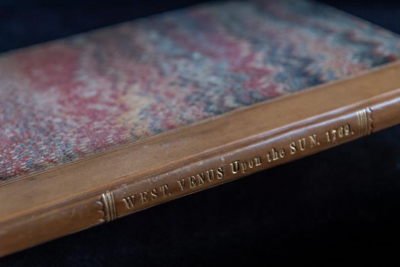 Detail of a bound book shows marbling on the boards and brown binding.