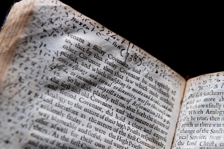Detail of a printed book shows text in English and manuscript notations throughout the margins.