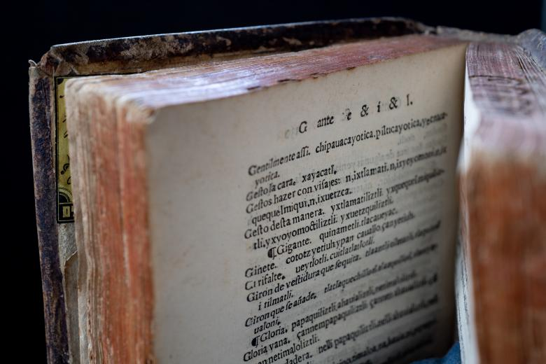 Detail of a printed book shows text in Spanish and Nahuatl.
