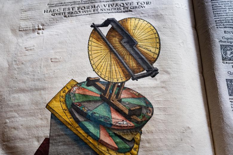 Detail of a printed books shows a colored illustration of a sun dial and text in Latin at the top of the page.