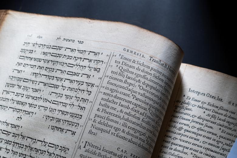 Detail of a page that is split in half. The left portion of the page is designated to text in Hebrew while the right side shows text in Latin.