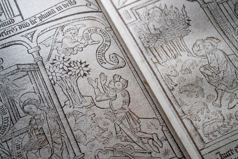 Detail of a blockbook shows woodcut illustration of an angel appearing to a kneeling knight. The angel carries a banner that has text in Latin.