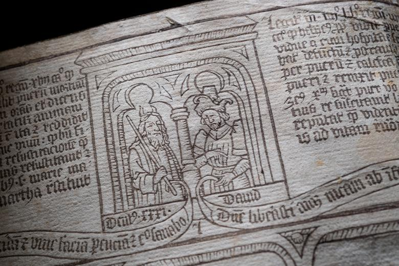 Detail of a blockbook shows woodcut headpiece illustration of two men talking. Text in Latin is also visible.