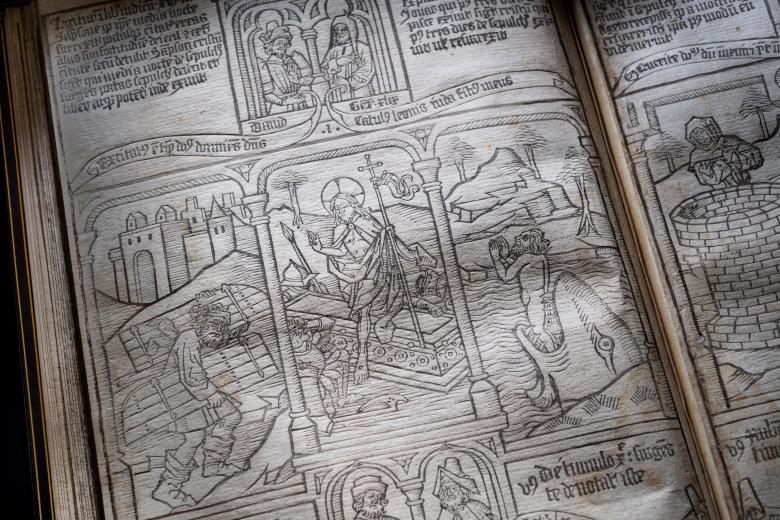 Detail of a blockbook shows woodcut headpiece illustration and biblical scene below. Text in Latin is visible.
