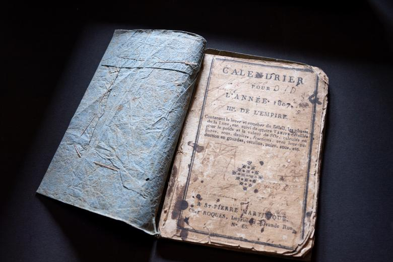stained title page of a printed pamphlet with a blue cover