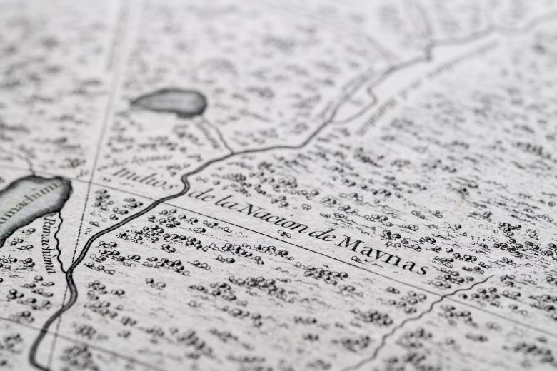 """Detail of a printed map shows text in Spanish reading """"Indios de la Nacion de Maynas."""" Rivers, small bodies of water, and forests are also included in the map."""