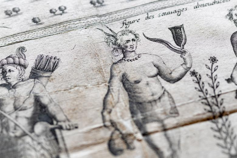 Detail of a printed map shows a topless woman holding something.