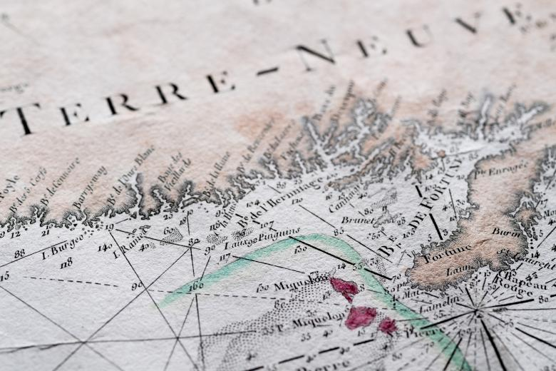 """Detail of a hand colored printed map shows text in French reading """"Terre-Neuve,"""" latitude and longitude lines, and labels over other geographical areas."""