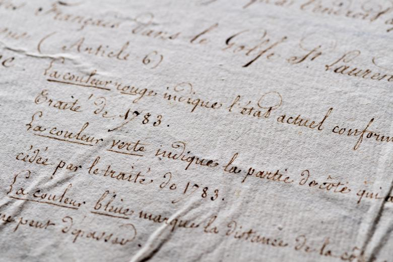 Detail of manuscript annotations on a hand colored printed map shows text in French.
