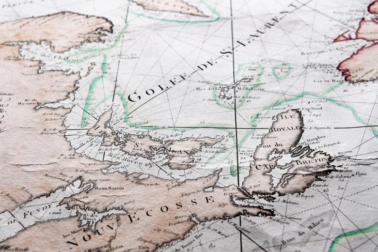 """Detail of a hand colored printed map shows text in French reading """"Nouv Escosse"""" and """"Golfe de S. Laurent,"""" among other labels. Latitude and longitude lines are also visible."""