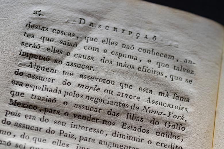 Detail of a printed page shows text in Portuguese.
