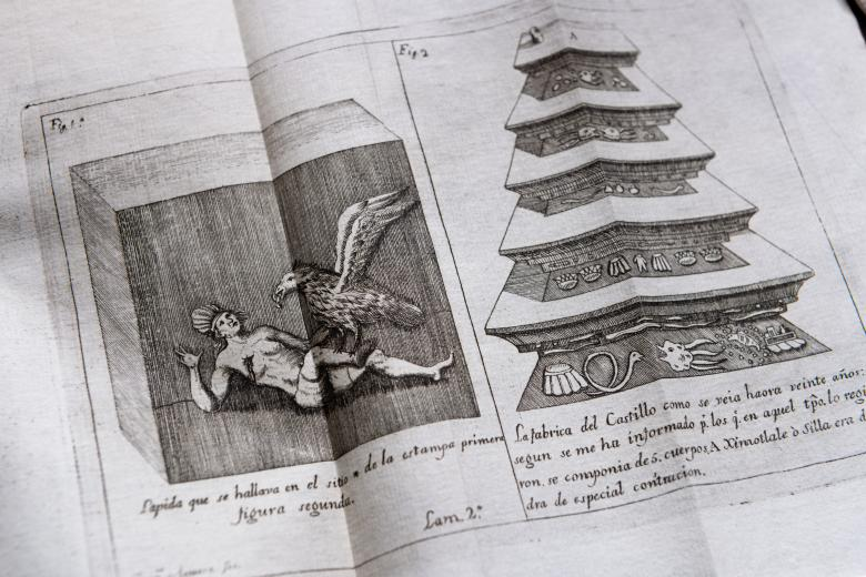 Detail from a printed book shows an illustration of a person lying on the floor being attacked by a large bird next to a diagram of a pyramid.