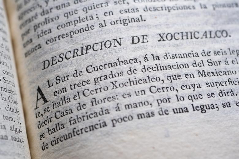 "Detail from a printed book shows text in Spanish reading ""Descripcion de Xochicalco."""
