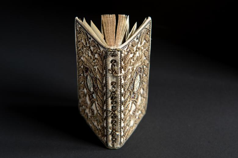 Book bound in white silk and decorated with the coat of arms of the Portuguese family and silver and gold beads.
