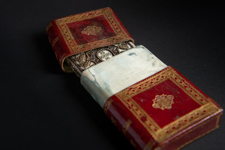 Book bound in white silk held in red Morocco box with gold ornaments on the covers.
