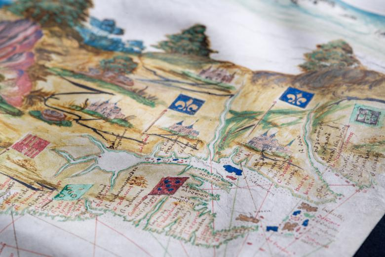 Detail of a hand colored manuscript map shows flags and place names along a coastal region.