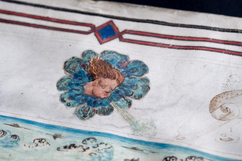 Detail of a hand colored manuscript map shows a wind head and a partial view of the map's decorative border.
