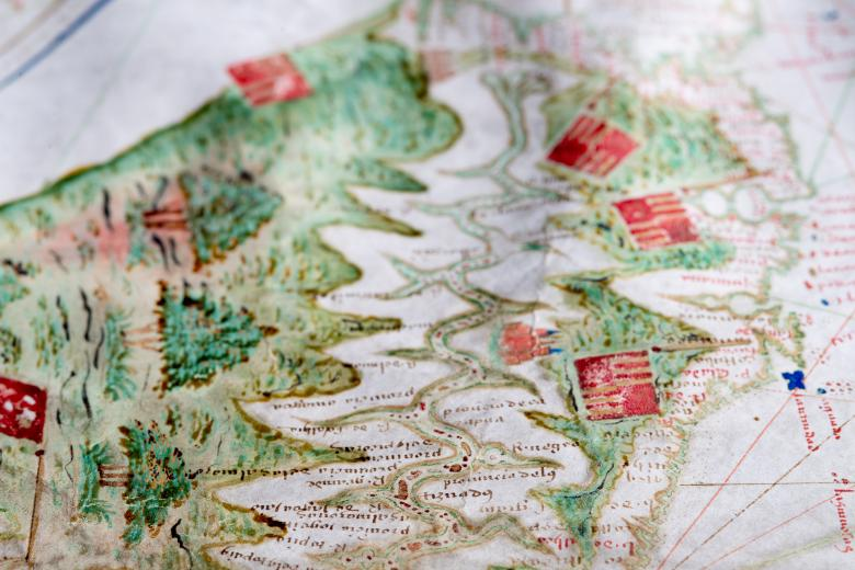 Detail of a hand colored manuscript map shows flags and trees along a coastal region.