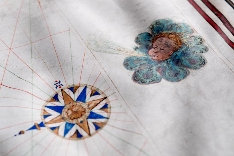 Detail of a hand colored manuscript map shows a wind head and a compass rose.