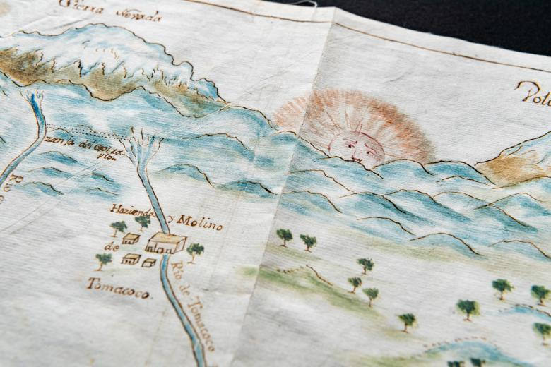 """Detail of a hand colored manuscript map shows locations labeled in Spanish such as """"Sierra Nevada"""" and """"Hazienda de Tomacoco."""" Personal estates, trees, the rising sun with a face drawn on it, and bodies of water are also included in the map."""