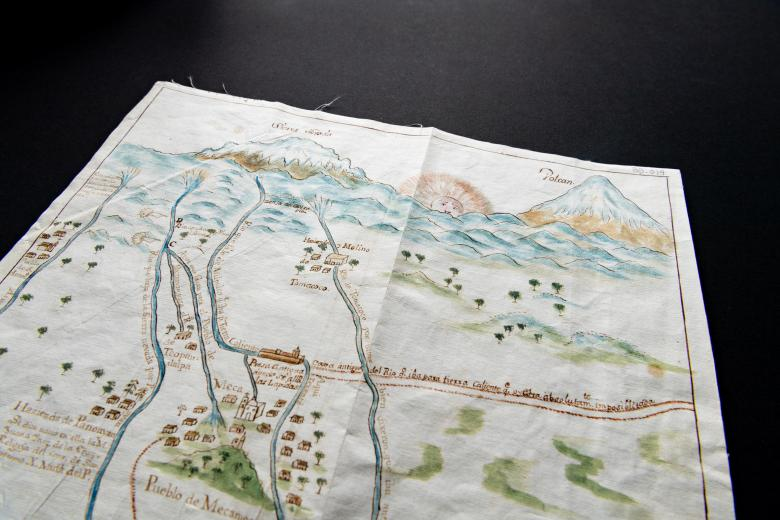 Detail of a hand colored manuscript map shows locations labeled in Spanish. Churches, trees, mountains, rising sun, and bodies of water are also included in the map.