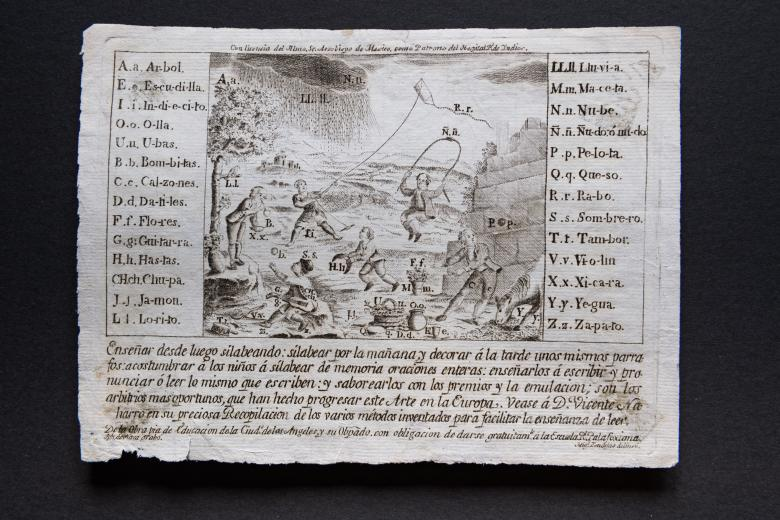 An engraved print shows Spanish and Native children playing with various objects which are labeled and identified in keys to the left and right edges of the print. Text in Spanish at the bottom of the print.