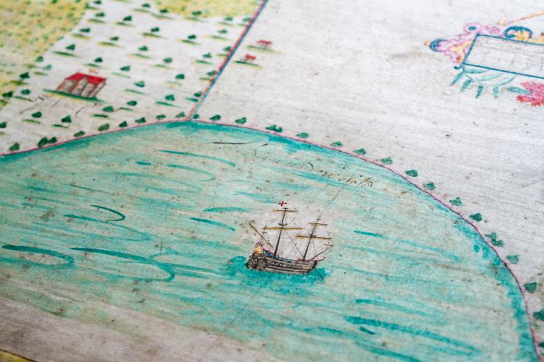 Detail of a hand colored manuscript estate plan shows a ship at sea and forest on land nearby.