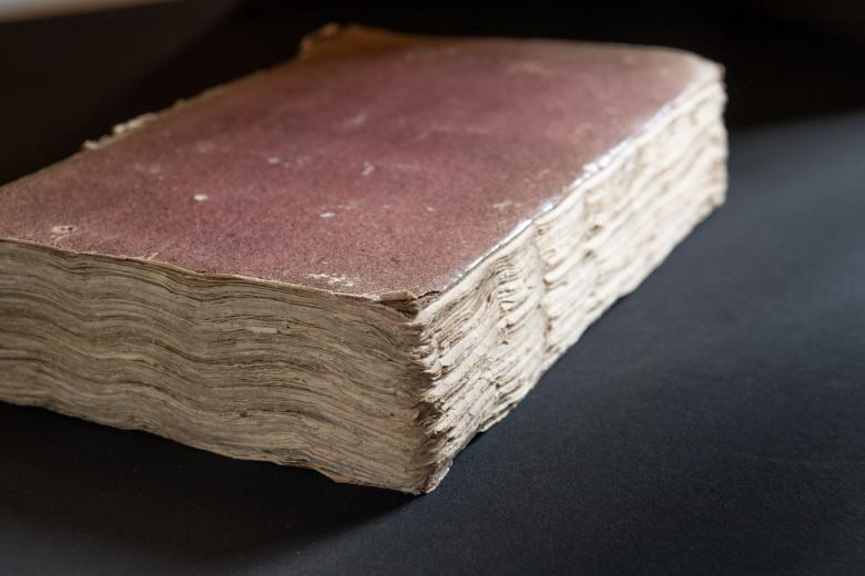 Printed book bound in brownish red boards also shows the worn and slightly warped pages of the book.