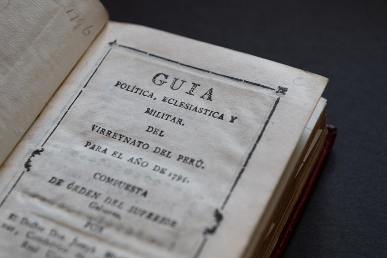 Detail of a printed book shows title page with the book's title written in Spanish.