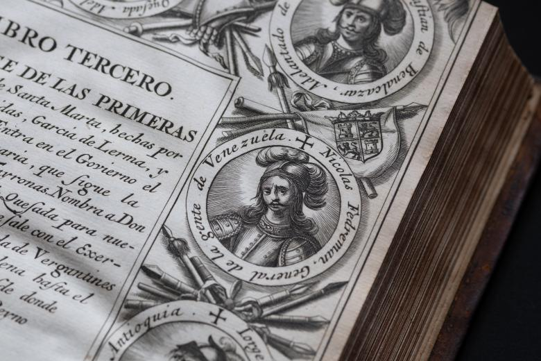 Detail of an engraved title page shows medallion portraits at the border, a coat of arms, and text in Spanish. Illustrations of flags and spears are also included in the border.