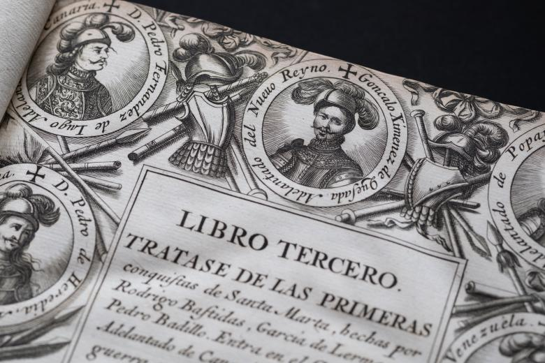 Detail of an engraved title page shows medallion portraits at the border, a coat of arms, and text in Spanish. Illustrations of the landscape are also drawn in the borders. Illustrations of spears, helmets, and shields are also included in the borders.