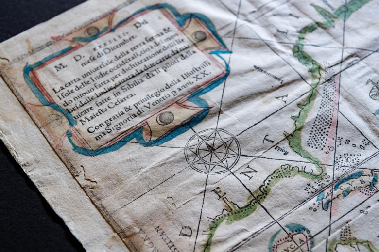"""Detail of a woodcut, hand-colored map depicting North and South America. Visible details include Cuba, written as """"CVBA"""", a compass rose, and text in Italian."""