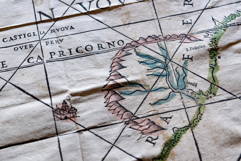 """Detail of a woodcut, hand-colored map depicting Tropic of Capricorn, shown as """"Capricorno,"""" a branching river painted blue, a mountain range painted a soft red color, and a small castle."""