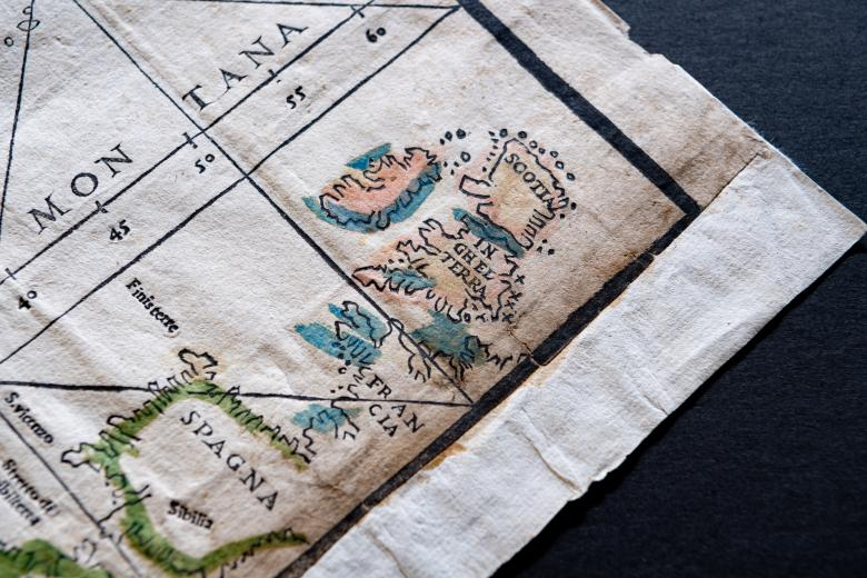 """Detail of a woodcut, hand-colored map depicting European countries Scotland (""""Scotia""""), England (""""Inghelterra""""), France (""""Francia""""), and Spain (""""Spagna""""). Italian text and small numbers indicate the altitude of geological features."""