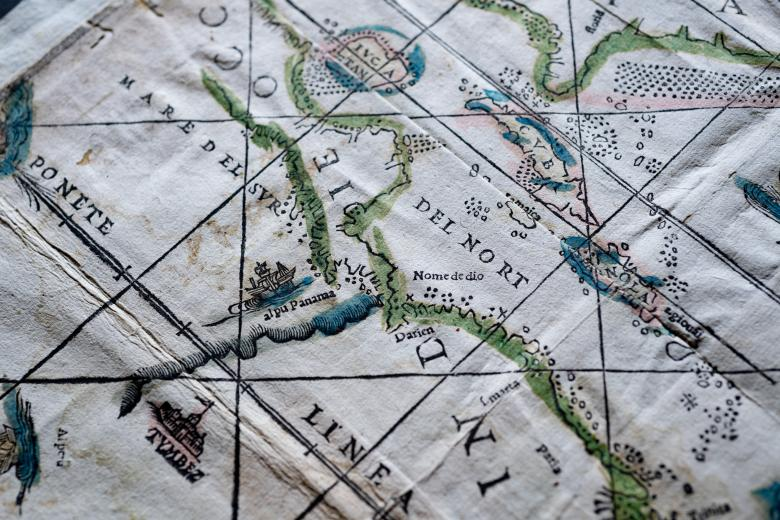 """Detail of a woodcut, hand-colored map depicting Cuba (""""Cvba""""), Yucatan (""""Ivcatan""""), and the Haiti and the Dominican Republic (""""Espanola""""). Other details include latitude and longitude lines, a castle, and a boat."""