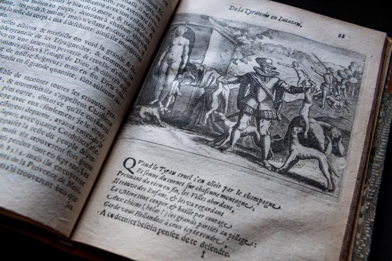 Detail of printed book shows illustration depicting a violent scene and text in French.