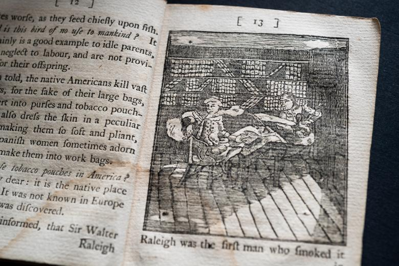 Detail of a printed book shows a full-page illustration of a man smoking while seated and another man throwing water on him. Text in English on the opposite page.