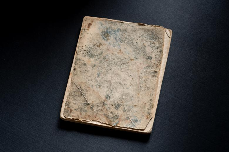 Faded and tattered marble paper binding on the front cover of a printed book.