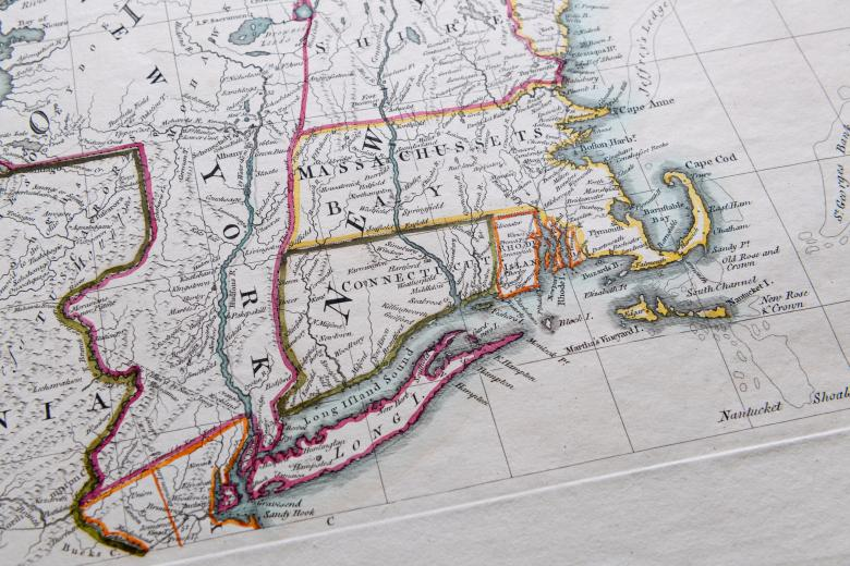 """Detail of a colored, engraved map shows pink, yellow, and green used to outline areas on the mainland and blue to color water. Labels in English over places such as """"Massachussets."""""""